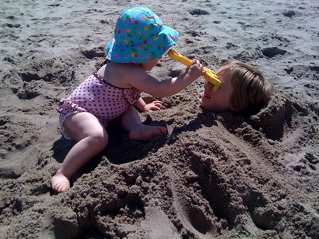 sis bury brother in sand